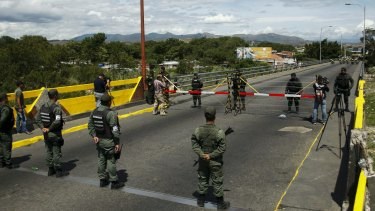Venezuelan National Guards (bottom) stand in front of Colombian soldiers on the Simon Bolivar international bridge, on the border with Colombia.