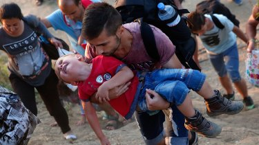 A young Syrian boy cries as his father carries him up a steep hill as they walk to a border crossing on the Greek and Macedonian border.