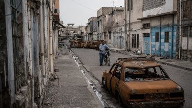 A man pushes his bicycle past burnt-out cars in a street in west Mosul.