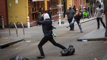 Members of the United Patriot Front throwing a bottle at a counter-protester.