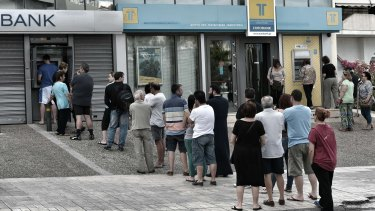 People stand in a queue to use ATM machines to withdraw cash at a bank in Athens.