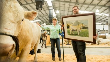 Australian pastoral: Livestock artist Jason Roberts with grazier Ann-Marie Collins and a $1000 portrait of one of her bulls, pictured at Royal Melbourne Show's livestock pavilion.