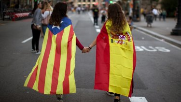 Irene Guszman, 15, wearing a Spanish flag on her shoulders and Mariona Esteve, 14, with an 'estelada' or independence flag, in Barcelona on October 3.