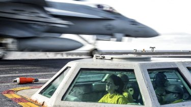 Here to stay: US Navy Lt. Michelle Mayer launches an F/A-18C Hornet from the bubble on the flight deck of the USS John C. Stennis in the Western Pacific.