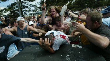 A mob surrounds and attacks a man of Middle Eastern appearance during the Cronulla riots.