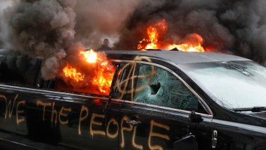 A parked limousine burns during a demonstration after the inauguration of President Donald Trump.