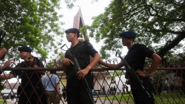 Officers guard a church compound following an attack during Sunday mass in Medan, North Sumatra.