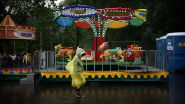 Rides go unridden as the rain pours down at the annual Lets Go Greek Festival in Parramatta.