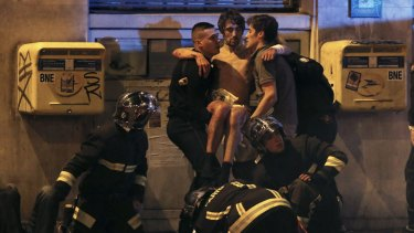 French fire brigade members aid an injured individual near the Bataclan following fatal shootings in Paris.