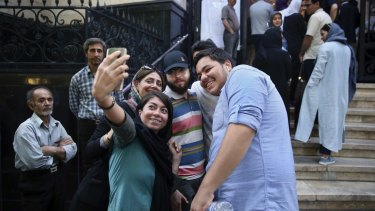 Friends take a selfie while lining up outside a polling station to vote for the presidential and municipal councils election in Iran.