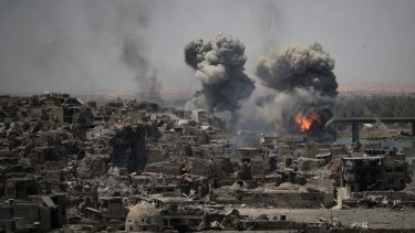 """In this July 2017 photo, airstrikes target IS positions on the edge of the Old City, a day after Iraq's prime minister declared """"total victory"""" in Mosul, Iraq."""