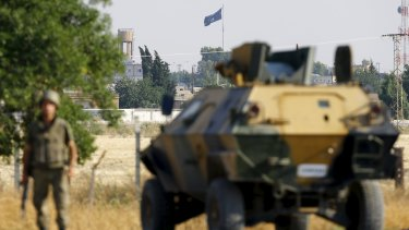 An Islamic State flag flies in the northern Syrian town of Tel Abyad in June, seen from the Turkish border town of Akcakale.