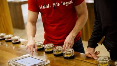 "An employee wears shirt reading ""Heal. It's Legal"" while helping a customer select marijuana strains at the MedMen dispensary in West Hollywood."