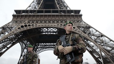 French soldiers patrol in front of the Eiffel Tower after terrorists killed at least 12 people at the Charlie Hebdo offices in Paris.