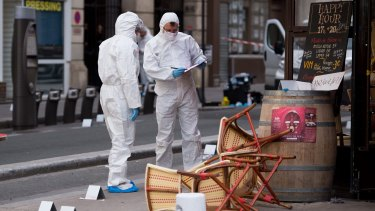 Police forensic experts work on the scene of one the shootings that took place in Paris at the Cafe Comptoir Voltaire.