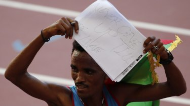 Ghirmay Ghebreslassie of Eritrea holds up a handwritten message after winning the men's marathon.