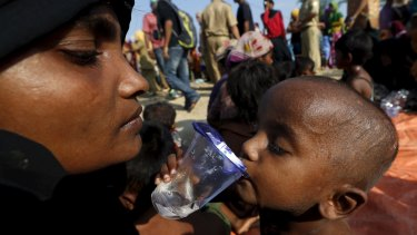 A Rohingya migrant mother watches as her child drinks water after they arrived in Indonesia by boat.