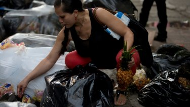 A pregnant woman who did not want to be named holds a pineapple in one hand as she continues to pick through garbage bags outside a supermarket in downtown Caracas.