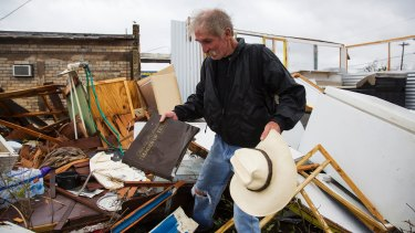 Harold Nubles searches through what is left of his barbecue truck in Refugio, Texas.