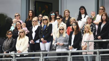 The wives and partners of the Australian team members look on in Cardiff.
