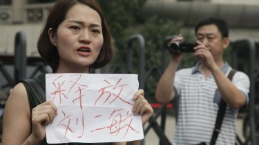 """A man films Li Wenzu, left, wife of imprisoned lawyer Wang Quanzhang, holding a paper that reads """"Release Liu Ermin""""  outside the Tianjin court on Monday.  Liu Ermin is a wife of one of the activists, who was arrested on Sunday, July 31."""
