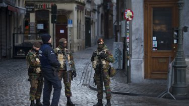 A police officer and armed soldiers stand guard at Grand Place square in Brussels, Belgium, on Monday as the search for a key suspect in the Paris terror attacks kept the Belgian capital in an unprecedented lockdown.