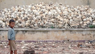 """July 1995: A Cambodian boy stands in front of  human skulls at a """"killing field"""" in Trapeang Sva Village, 25 kilometres south of Phnom Penh."""