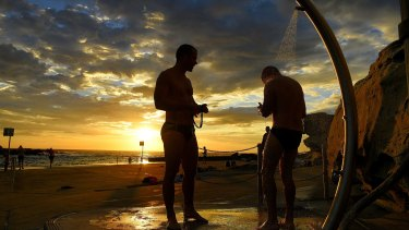 Swimmers rinse off at Clovelly Beach before the temperatures rise in Sydney on Tuesday morning.