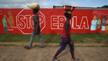 People pass an Ebola awareness mural in Monrovia, Liberia. More than 3,200 people have died in West Africa due to the epidemic.