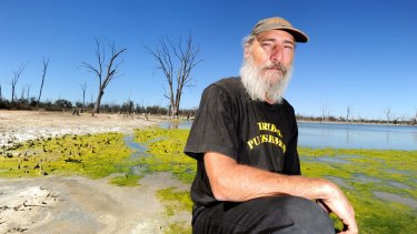 Darren Perry at Psyche Bend Lagoon, near Mildura. In background is algae forming as a result of high water temperatures and low oxygen.