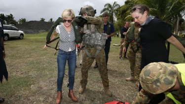 A crewman helps Foreign Affairs Minister Julie Bishop put on her lifejacket for a helicopter ride to Rakiraki during her visit to areas affected by Tropical Cyclone Winston.