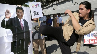 A protester kicks a portrait of Chinese President Xi Jinping outside the office of Taiwanese President Ma Ying-jeou on Thursday.