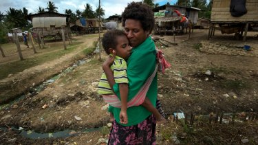 Soba holds her son Sawai Naruwa, who has lost the use of his legs as a result of tuberculosis in Daru in 2011.