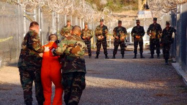 High security: Police escort a detainee to his cell in Guantanamo Bay in 2002.