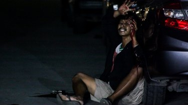 Francisco Maneja, bleeding from gun shot wounds, raises his hands to ask for help in Manila.