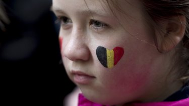 A child looks on during a vigil for the victims of the Brussels attacks at the Belgium Consulate in Montreal, Canada, on Wednesday.