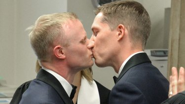 Benjamin Moore and Tadd Roberts kiss after their marriage ceremony in Louisville, Kentucky.