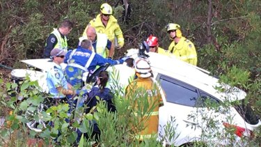 Emergency services officers work to cut Samuel Lethbridge from the wreck of his car.