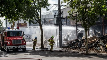 Fire crews continue to hose-down smoldering remains of the market on Wednesday morning.
