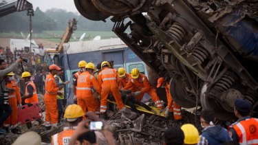 Rescuers pull out a body from the debris of an overnight passenger train disaster in India on Sunday.