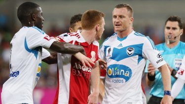 Jason Geria of the Victory tries to play peacemaker as Nick Hegarty of Hume City and Besart Berisha of the Victory get into a verbal stoush.