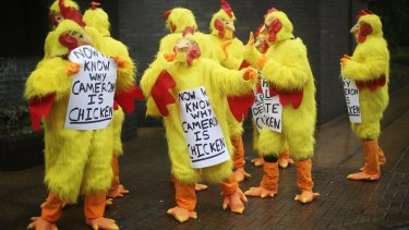 Protesters await Prime Minister David Cameron as he addresses delegates at the Conservative Party's spring forum.
