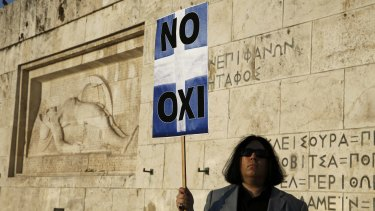 A protester holds a banner in Greek colours in front of the parliament building during an anti-austerity rally in Athens, Greece on Monday.
