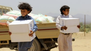 Displaced Yemeni children, who fled with their family from the city of Sirwah due to the fighting between Houthi rebels and militiamen loyal to Yemen's fugitive President Abderabbo Mansour Hadi, carry boxes of humanitarian aid donated by UNICEF on Monday.