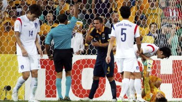 Tim Cahill (centre) reacts as he is given a yellow card after a foul on South Korea's goalkeeper Kim Jin-hyeon (right) during the Asian Cup Group A match in Brisbane on Saturday.