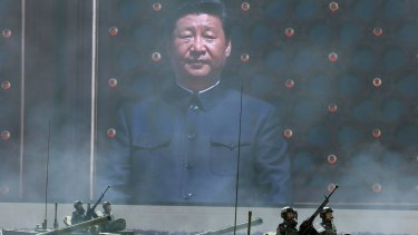 Chinese President Xi Jinping is displayed on a big screen as Chinese battle tanks parade  below.