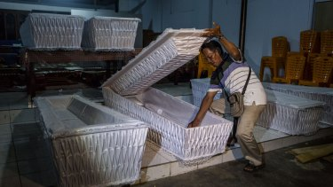 A man prepares coffins before loading them into a truck ahead of the executions of the death row inmates in coming days.