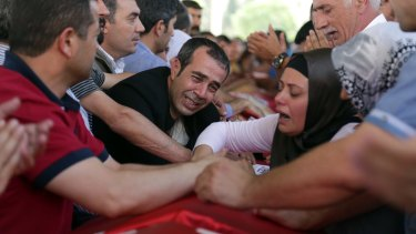 Relatives and friends mourn over the coffins of victims of the attack.