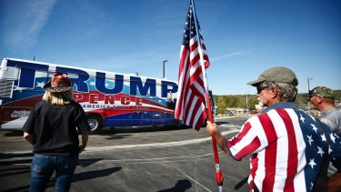 Supporters stand near Donald Trump's bus during a campaign stop last October in Alabama, home state of the writer's cousin.
