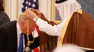 Saudi King Salman presents President Donald Trump with the Collar of Abdulaziz Medal in  Riyadh.